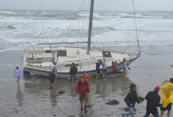 Lynn: Boat owner Steve Banks of Swampscott, center, walks away from his boat that drifted to King's Beach after breaking loose from its mooring in the Swampscott harbor during Tropical Storm Irene.   photo by Mark Teiwes / Salem News