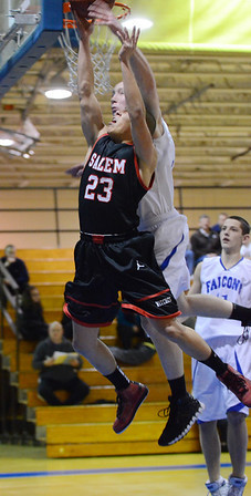 Danvers: Salem's Edgardo goes strong to the board fouled by Danvers player Sean Mahegan.  photo by Mark Teiwes  / Salem News