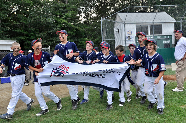 Beverly: Peabody West team carries the District 15 Little League championship flag.  Bobby Caproni, right, had the game winning hit off a fastball.  He said he was pretty nervous but the coach just told him to hit it.   Mark Teiwes / Salem News