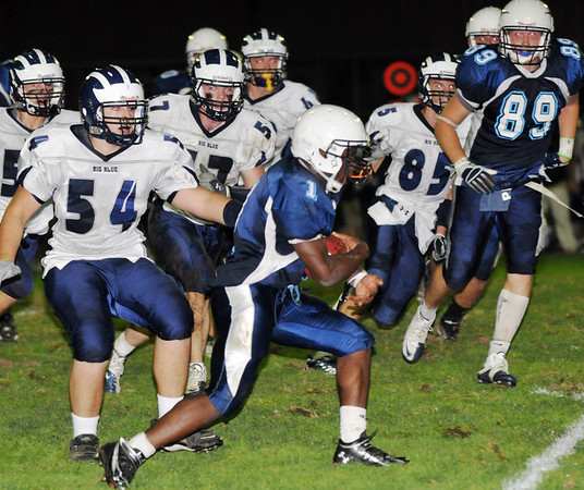 Peabody: Peabody High School running back Nat Gaye, right, finds an opening in the Swampscott defense passing #54 Patrick Sheehan.  photo by Mark Teiwes / Salem News