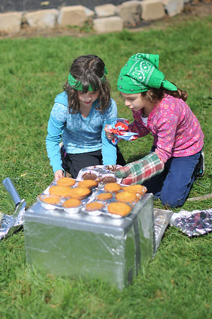 Danvers: Girl Scout Brownies Sofiya Palermo, left, and her sister Catarina, both 7-years-old help make cupcakes in an oven made from a carboard box, tin foil with heat from the coals of a camp fire.  Girl Scouts will be celebrating its 100th anniversary in 2012. The Girl Scouts in Danvers started the celebration camping at Endicott Park and playing games from the turn of the 20th century.  photo by Mark Teiwes  / Salem News