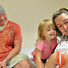 Salem:  Proud father Chris Szczechowicz, left, 2-year-old Lola, and mother Abi admire newborn baby Emma who was born at home Friday morning. photo by Mark Teiwes / Salem News
