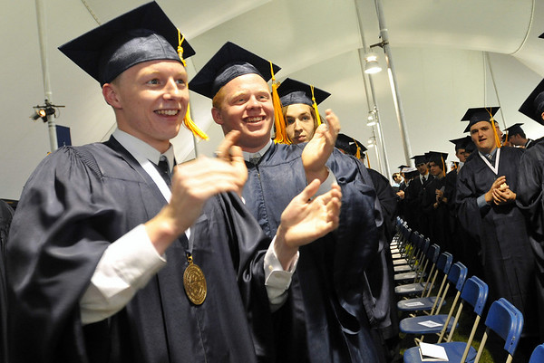 Danvers: Steven Hayes, left and Mark Hefford clap as their teachers come in during the processional for the 100th commencement ceremony at John's Prep.  Photo by Mark Teiwes / Salem News