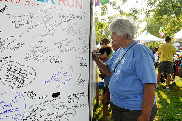 Salem:  Sheila Griffin signs a remembrance board at the start of North Shore Cancer Walk.  photo by Mark Teiwes / Salem News