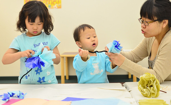 Hamilton: Amy Cho of Hamilton works on making paper flowers with her daughter Sud, 6, and son Han, 2, at a Mother's Day event at the Hamilton-Wenham Public Library.  Mark Teiwes / Salem News