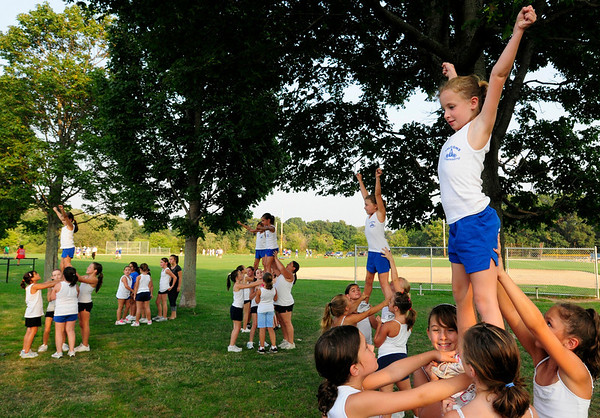 Danvers: Kate Evans, 8, of Danvers acts as the flyer while practicing stunts for cheerleading. photo by Mark Teiwes / Salem News
