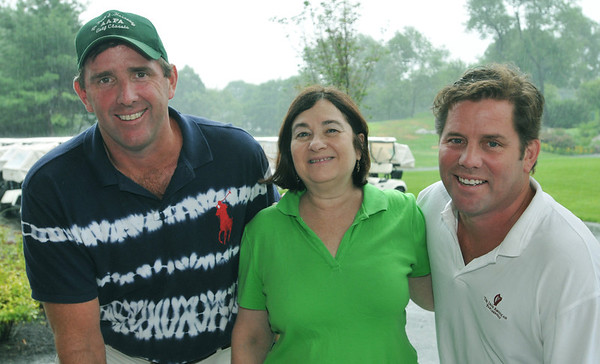 Marblehead: Brothers Kevin, left, and Tod Hannaway, right, stand with Elaine Rosenburg, executive director of the Asthma Allergy Foundation of America, New England Chapter for the Paul Hannaway Memorial Golf Classic.  photo by Mark Teiwes / Salem News