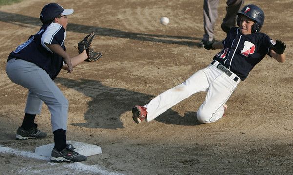 Lynn: Peabody West player Jake Doherty, right, slides safe into third base beating a throw caught by Peabody Amercan's Sean Mullins.   photo by Mark Teiwes  / Salem News