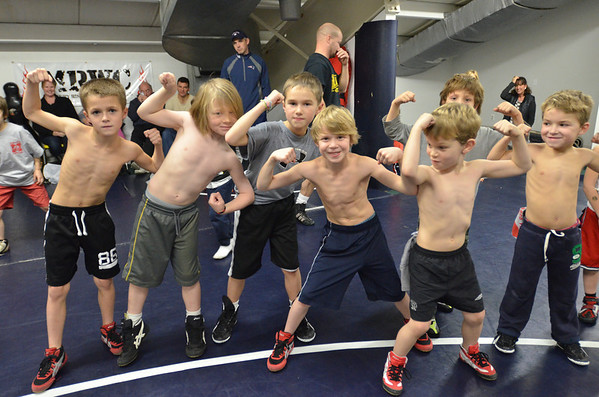 Danvers: Wrestling clinic participants flex prior to a game of fox tail.    photo by Mark Teiwes / Salem News