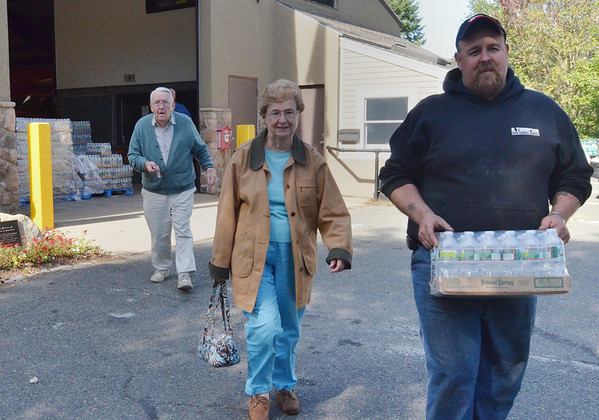 Wenham: Sean Reed, Wenham DPW mechanic carries water for Tony and Virginia Waller.  photo by Mark Teiwes / Salem News