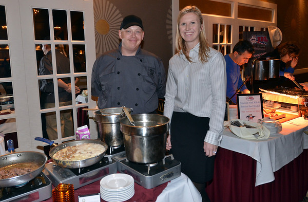 Danvers: John Andrews, left, cooked up food from Victoria Station restaurant.  Rose Fisher, right, of the North Shore Medical Center walk, attended enjoyed the food from more than ten area restaurants.   photo by Mark Teiwes / Salem News