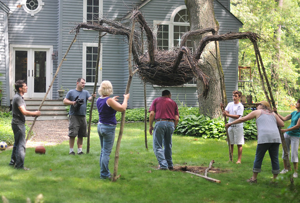 "Hamilton: Allan Brockenbrough, left, directs a team in the placement of   a spider with 10 foot long legs made out of branches outside his house.  ""Art Grows Here,"" is a self-guided tour of art installations throughout Hamilton and Wenham next week.  photo by Mark Teiwes / Salem News"