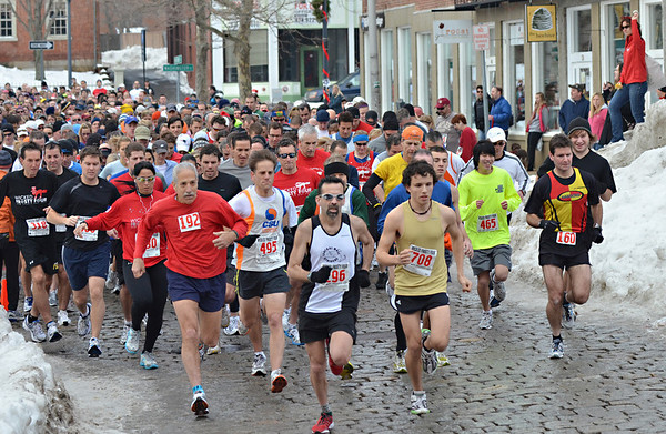 Salem: About 750 runners take off down Front Street from the starting line of the Wicked Frosty Four road race on New Year's morning.  Alex Gomes (708) jumped to an early lead and went on to win the race.  photo by Mark Teiwes  / Salem News
