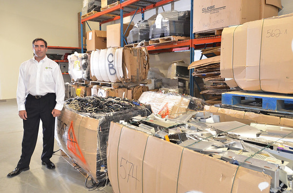 Danvers:  David Saia of XTechnology stands in a warehouse with disassembled computer parts that will be recycled. photo by Mark Teiwes / Salem News