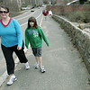 Beverly: Allison Loft and her daughter Sophie, 8, of Beverly stroll past Endicott College on the 32nd annual Good Friday Walk.   photo by Mark Teiwes / Salem News