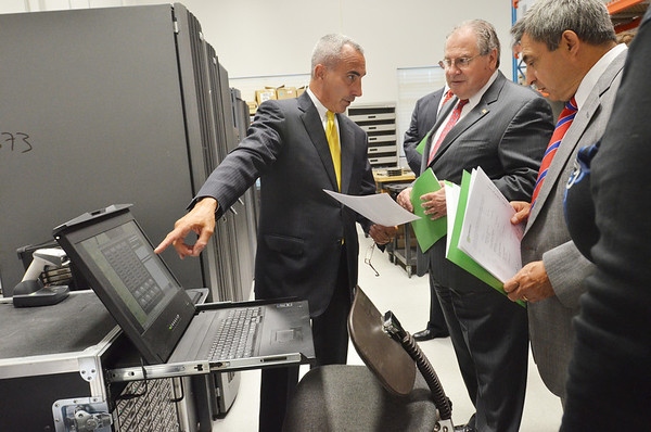 Danvers:  XTechnology CEO Michael Saia, left, shows Massachusetts House Speaker Robert A. DeLeo, and Representative Ted Speliotis a piece of equipment in the company's data compliance lab.  photo by Mark Teiwes / Salem News