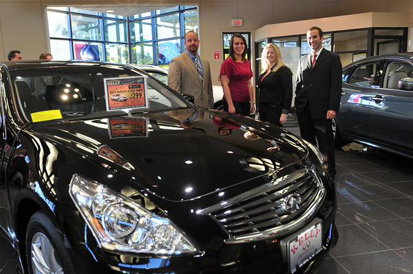 Danvers: Greg Bath of Infinity Corporate, left, Brittany Nelson of Danvers, Kristen MacLeod of Peabody and Brian Heney, executive manager at Kelly Infiniti stand behind the new G25X model.    photo by Mark Teiwes / Salem News