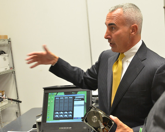 Danvers:   XTechnology CEO Michael Saia describes how his company specializes in removing sensitive data from hard drives and storage devises.  photo by Mark Teiwes / Salem News
