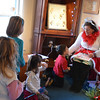 "Marblehead:  Marguerite Frank, right, reads the book ""Elf on the Shelf"" to Lilly Jones, 6, left, her sister Madison, 7, of Marblehead, Ella Karlin, 4, and her brother Theo, 3, of Swampscott, at the Seagull store. photo by Mark Teiwes /  Salem News"
