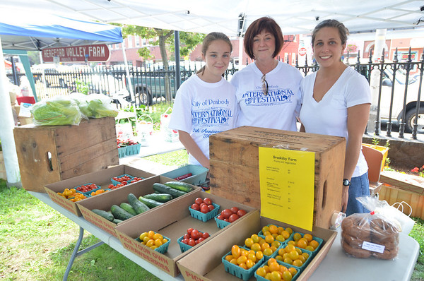 Peabody: Emily Bellavance, 13, left, sells produce from Brooksby Farm with her mother Mary and Lucia DelNegro during a farmers' market at the Peabody Institute Library.    photo by Mark Teiwes /  Salem News