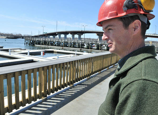 Beverly: Mike Collins, Beverly's commissioner of public services and engineering, stands on a seawall and concrete deck nearing completion that replaced a wooden pier on the waterfront.  photo by Mark Teiwes / Salem News