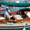 Salem: Harvey Schwartz of Ipswich relaxes on his Pease Boat Works sailboat  during the Antique and Classic Boat Festival.  Daniel Rowe and Lisa Brooke of Salem paddle by in kayaks getting a water level view of the festival.  photo by Mark Teiwes / Salem News
