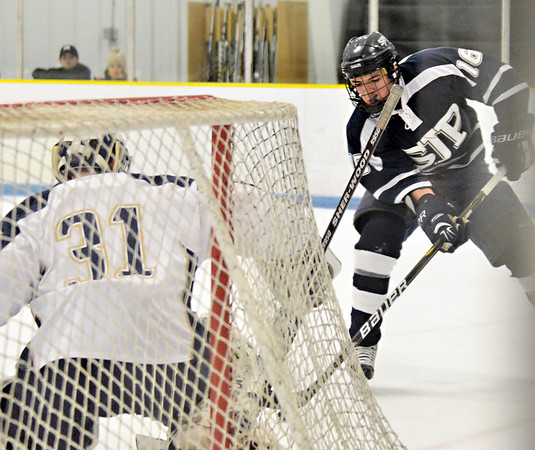 Malden: St. John's Prep forward Sam Kurker attacks the goal attended by Malden Catholic's Pat Young.  photo by Mark Teiwes  / Salem News