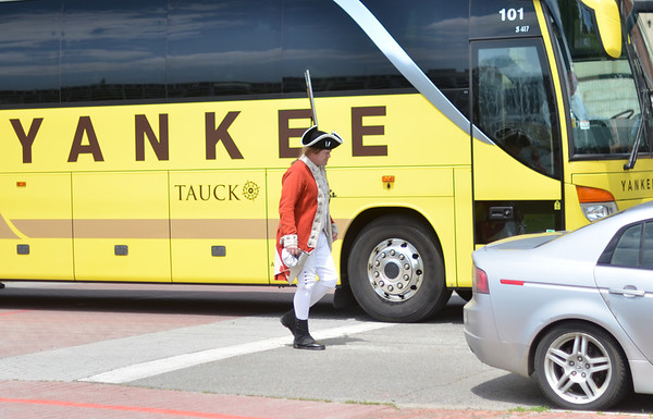 Salem: Dave Parker of West Newbury plays a British soldier patrolling along Derby street as a tourist bus drives by.   photo by Mark Teiwes / Salem News
