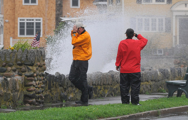 Salem:  A couple walks down Columbus Avenue as high tide waves crash over the wall during Tropical Storm Irene.   photo by Mark Teiwes / Salem News