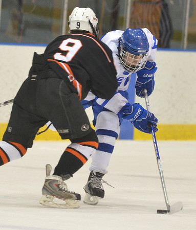 Salem: Beverly's Matt Hamor puts a body check on Danvers' Nick Strangie.  Matt Hamor scored one of Beverly's goals.  photo by Mark Teiwes  / Salem News