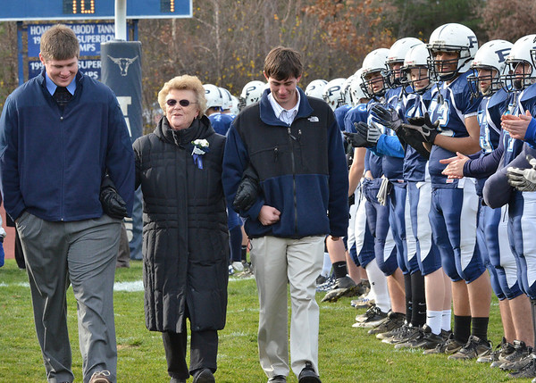 Peabody: Prior to the Thanksgiving Day football game, Ann Boyle Flynn, center, walks with her grandsons Mike Charochak, left, and Dan O'Connell, right, as she is recognized as a class of 1950 Peabody High School hall of fame inductee for basketball. photo by Mark Teiwes / Salem News