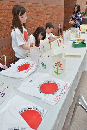 Salem: Zoe Poussard-Barham, 11, left,  Elodie Poussard, 8, Freddie Poussard, 8 and their mom Lauren Poussard run a clothing drive, sell tee shirts the kids designed, and make cards to send to Japan. photo by Mark Teiwes / Salem News