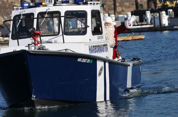 Danvers: Santa arrives along the Porter River in the Danvers harbormaster's boat.  photo by Mark Teiwes / Salem News