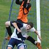 Peabody:  Salem goalie Danny McCarthy makes a save on a corner kick and lands on Peabody's John Ramsey.  photo by Mark Teiwes / Salem News