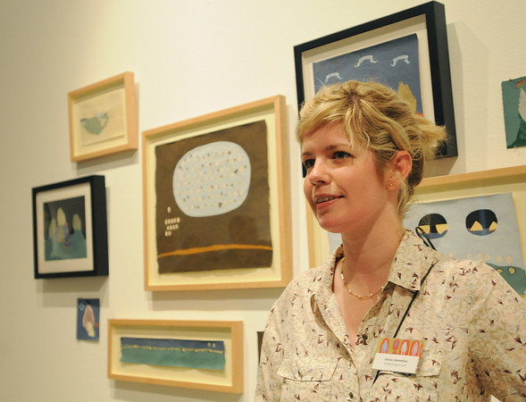"""Beverly: Artist Alexia Stamatiou of Brookline stands in front of her gouache and ink on paper """"Rabbit War"""" series at a Montseratt exhibition.  photo by Mark Teiwes / Salem News"""