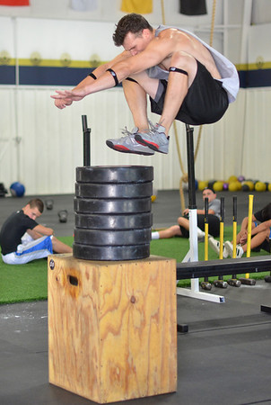Danvers:  Mark Wilson, All American wide receiver from Saint Anselm College, leaps on top of a stack of weights at Gridiron Training. photo by Mark Teiwes /  Salem News