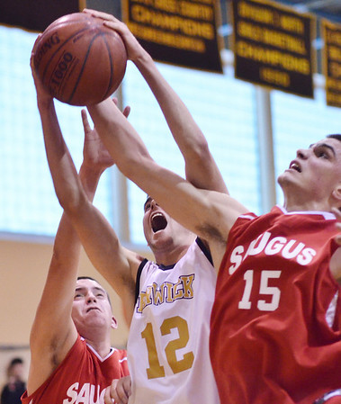 Peabody: Bishop Fenwick forward Mike LaChance, center, struggles for a rebound challenged by Saugus players Jimmy Hyde, left, and Andrew Turgeon.  photo by Mark Teiwes  / Salem News