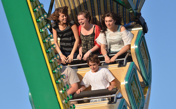 Beverly:  Angela Miller, 17, of Beverly, left, Lydia Hester, 15, of Danvers, Abi Cissel, 17, of Lynfield, and Anthony D'Amato ride the Pharoh's Fury.  Carnival rides spin on the grounds of Beverly High School till Sunday.  Proceeds benefit the Beverly Education Foundation.  photo by Mark Teiwes / Salem News