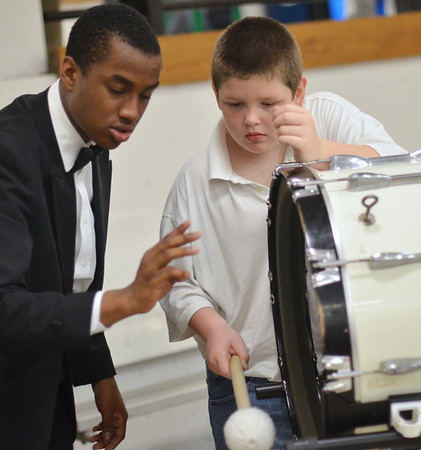 Salem: Salem High School junior Jabari Tovar, left, helps fifth grader Steven Gibney stay on beat with the bass drum during a school performance.   photo by Mark Teiwes / Salem News