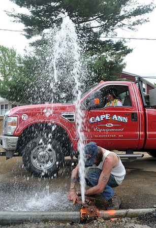 Danvers: A worker from Cape Ann Equipment repairs a temporary water main after a trailer backed into it causing a geyser on Riverside Rd.  photo by Mark Teiwes / Salem News