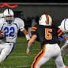 Beverly:  Danvers running back Nick Valles, left, sprints and stares down Beverly's Dom Abate blocked by T.J. Stanley, right.   photo by Mark Teiwes / Salem News
