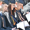 Beverly: Josh Carmer, left, Hayley Carlotto, and Adam Capodilupo take a look for the first time at their Beverly High School diplomas.  photo by Mark Teiwes / Salem News