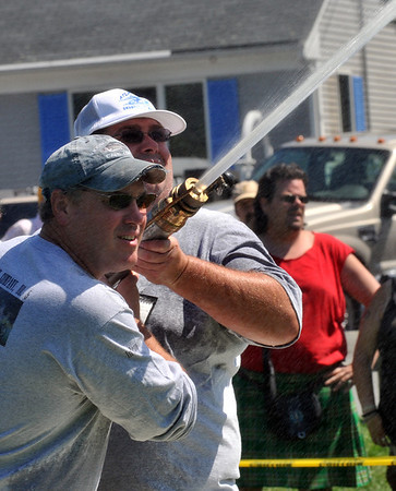 Marblehead:  Dirk Martin of Marblehead, left, and Mike Butler of Swamscott act as pipemen holding the playpipe nozzle directing the stream of water at an old fashioned fireman's muster.  photo by Mark Teiwes / Salem News