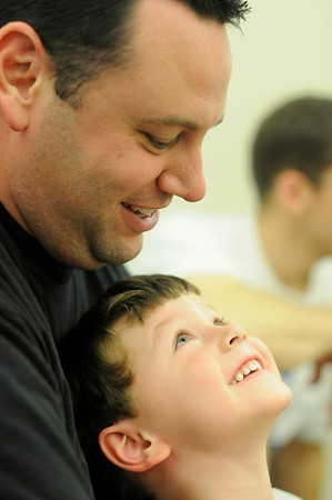 Hamilton: 3 year old Emmett Snyder of Peabody looks up at Scott his father during a library program especially for dads and children.  photo by Mark Teiwes / Salem News