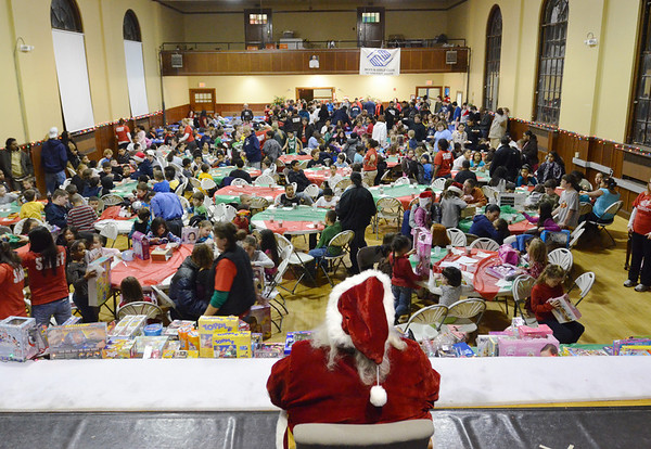 Salem: Santa watches over a table of Christmas gifts made possible by St. John's Prep student council and the Wicked Running Club of Salem for a Christmas party at Boys and Girls Club of Greater Salem. photo by Mark Teiwes  / Salem News