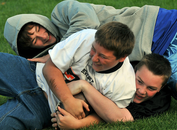 Danvers: Jake Shairs, left, wrestles for the football with his cousins Kolbi and Nicholas.    photo by Mark Teiwes / Salem News
