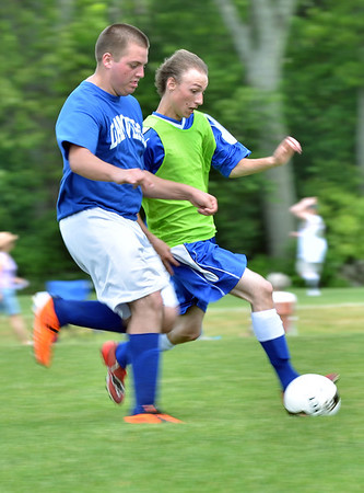 Hamilton: Sean Harrison of the Danvers Revolution, left, battles for the ball with Don Bibbo of the Methuen Blitz at the Essex Country Youth Soccer playoffs. photo by Mark Teiwes / Salem News