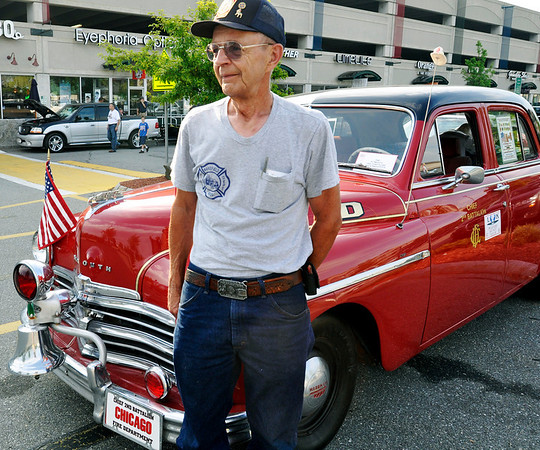 Beverly: During cruise night at the American BBQ, Raymond Pitts, of Beverly, stands next to his 1949 Plymouth, a replica of a Chicago fire department car.  photo by Mark Teiwes / Salem News