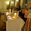 "Danvers: Lis Carey, left, lights a candle with her dog Addy below the alter during ""Perfect Paws"" pet ministry lead by the Rev. Thea Keith-Lucas, right, at Calvary Episcopal Church. photo by Mark Teiwes / Salem News"