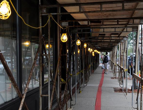 Salem: A pedestrian passes through scaffolding put up along Washington for building improvements.  photo by Mark Teiwes / Salem News
